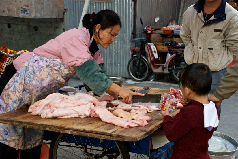 A young boy helps his father buy meat at the street market.